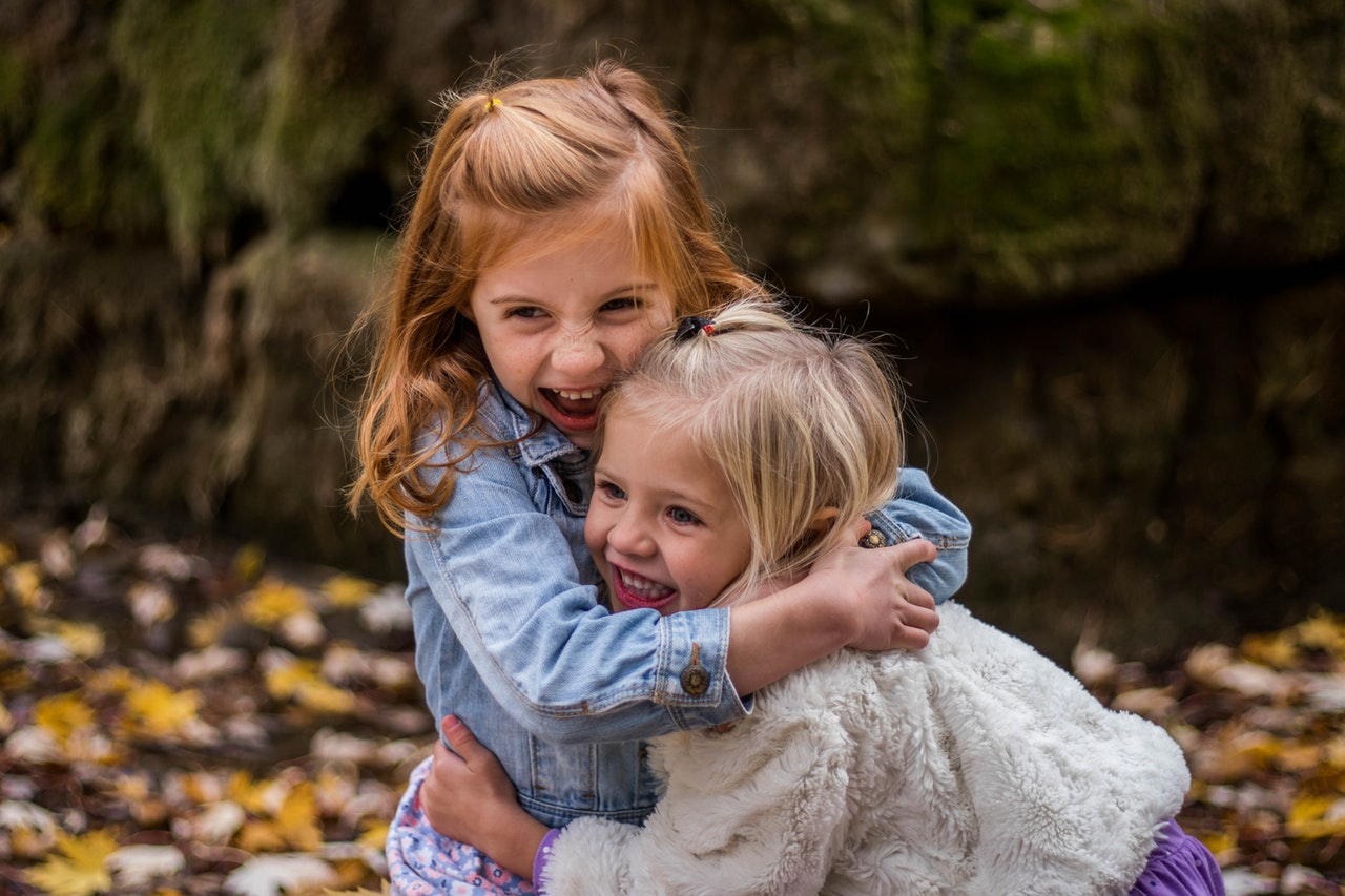 2 children hugging outdoors during playtime. connection helps promote mental health.